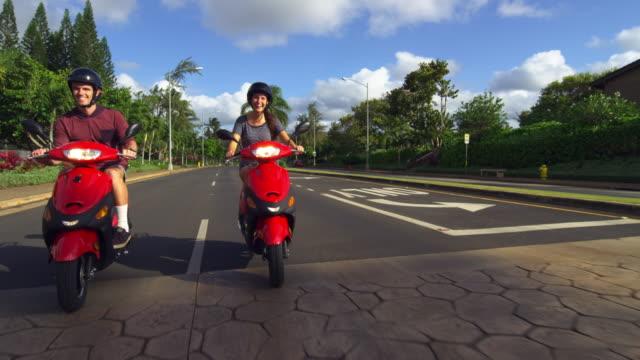 a couple on mopeds drive past camera - タートル湾点の映像素材/bロール