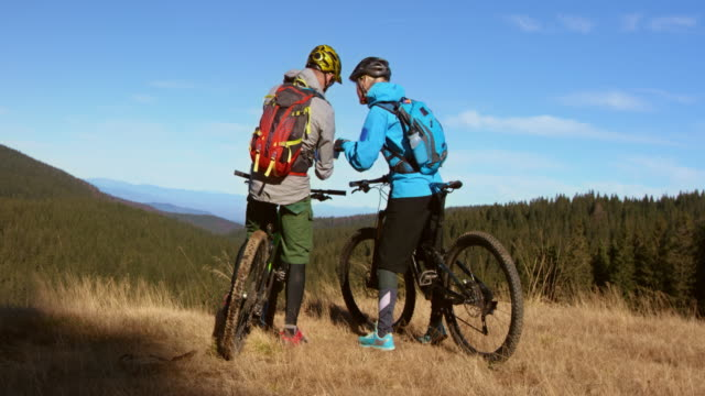 Couple on mountain bikes discussing their position