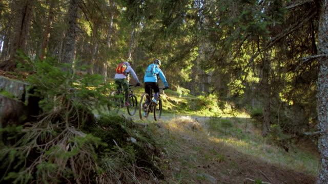 vidéos et rushes de slo missouri couple sur les vélos à cheval à travers la forêt - faire du vélo tout terrain