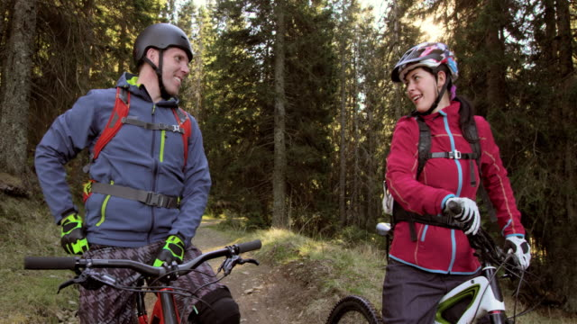 Couple on mountain bikes stopping on forest trail while talking
