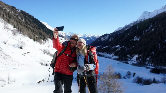 stockvideo's en b-roll-footage met couple on mountain top take selfie, snowy valley below - ski jack