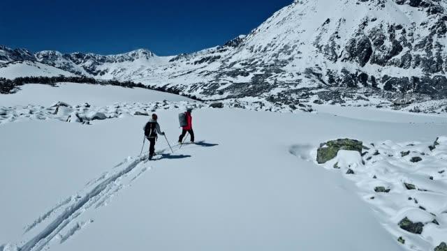 couple on mountain trail. ski touring in winter wonderland. aerial view - alpinismo video stock e b–roll