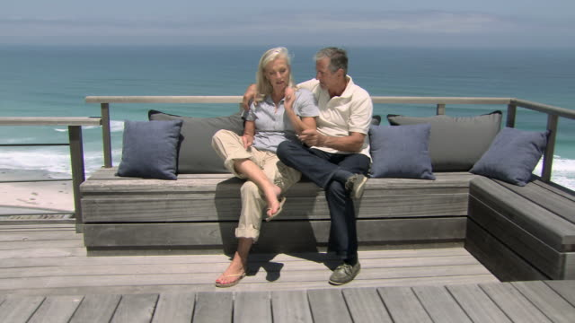 couple on seat near the sea - beach house stock videos & royalty-free footage