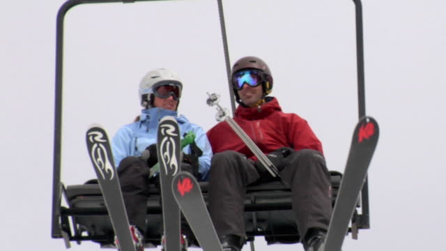 cu, la, couple on ski lift moving up mountain, whitefish, montana, usa - winter sport stock videos & royalty-free footage