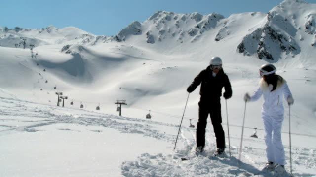 Couple on slope starting to ski, beautiful panorama