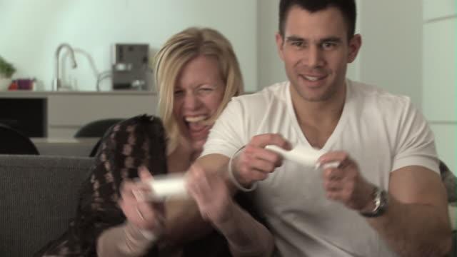 vídeos de stock, filmes e b-roll de ms couple on sofa playing videogame / copenhagen, denmark - países nórdicos