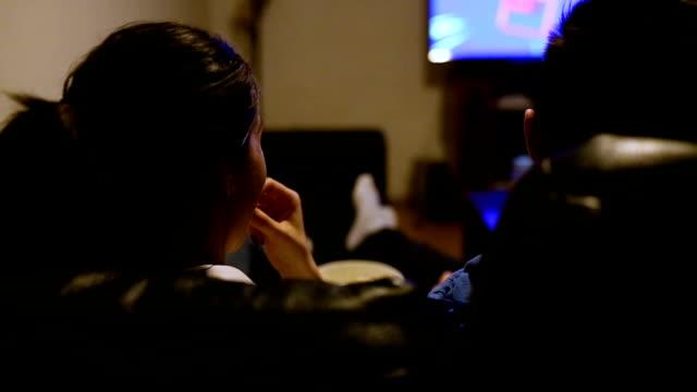 vídeos y material grabado en eventos de stock de pareja en el sofá con control remoto del televisor - mirar un objeto