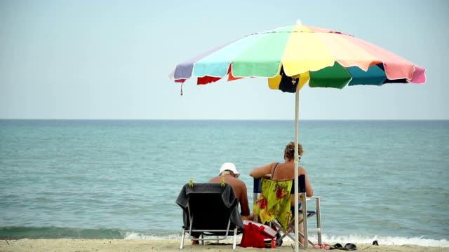 vídeos de stock, filmes e b-roll de casal na praia. - chapéu de sol