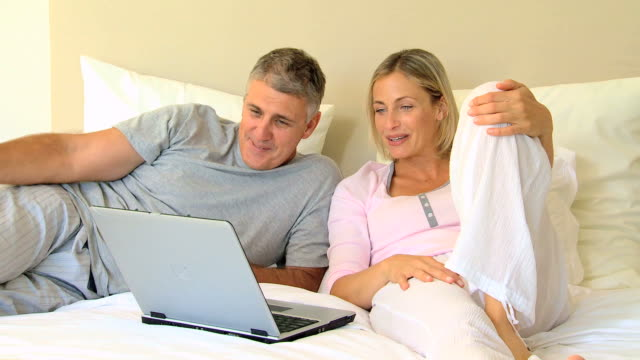 couple on the bed with a laptop / cape town, western cape, south africa - 横向きに寝る点の映像素材/bロール