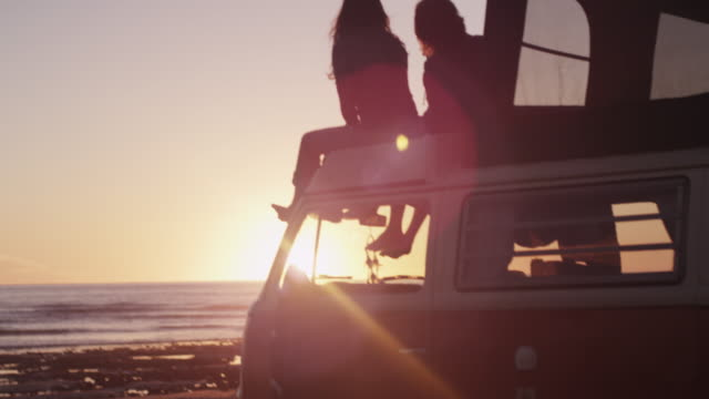 Couple on van roof, scenic beach sunset