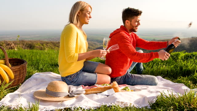 Couple opening a bottle of wine during picnic