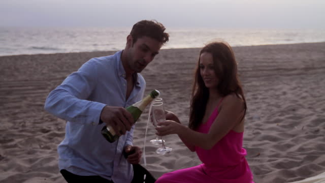 Couple opens a bottle of champagne on beach