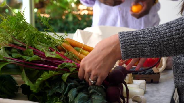 vídeos y material grabado en eventos de stock de cu couple organizing fresh organic vegetable and fruit on kitchen counter after shopping - conservacionista