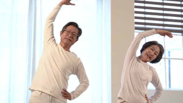 couple over 60 stretching together in couple clothes in the living room - south korea couple stock videos & royalty-free footage