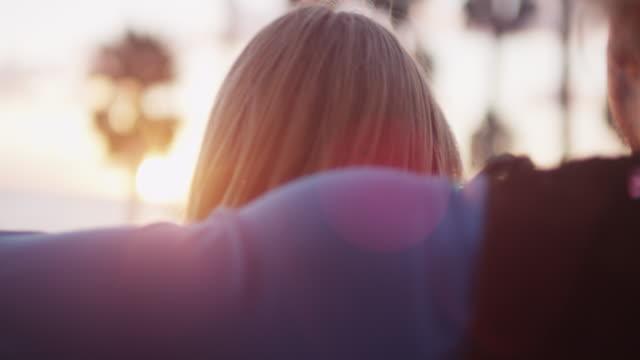 couple overlook coastal sunset, slow motion - 帽子点の映像素材/bロール