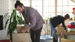 Couple packing things in cardboard boxes