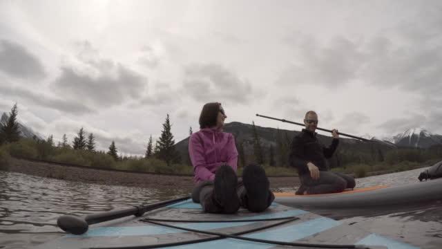 vídeos de stock e filmes b-roll de couple paddle boards across alpine lake - gola alta