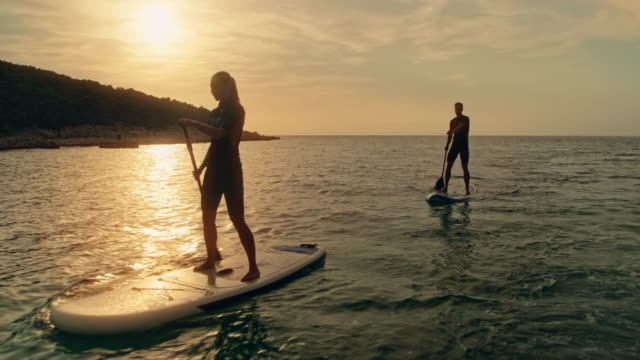 couple paddling on their sups at sunset - oar stock videos & royalty-free footage