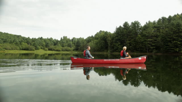 ws couple paddling their canoe across lake / stowe, vermont, united states - vermont stock videos & royalty-free footage