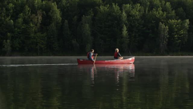 vídeos y material grabado en eventos de stock de  ws couple paddling together across a lake / stowe, vermont, united states - pareja de mediana edad