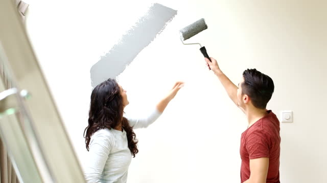 couple painting wall with paint roller and kissing - paint roller stock videos & royalty-free footage