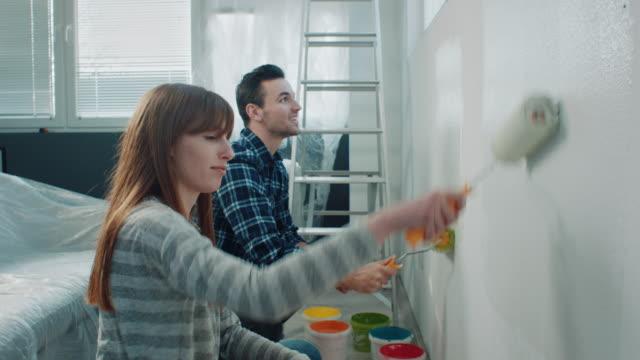 夫婦畫牆在他們的新房子 - 裝飾 個影片檔及 b 捲影像