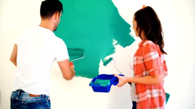 vídeos de stock, filmes e b-roll de paredes de pintura do casal. - parede