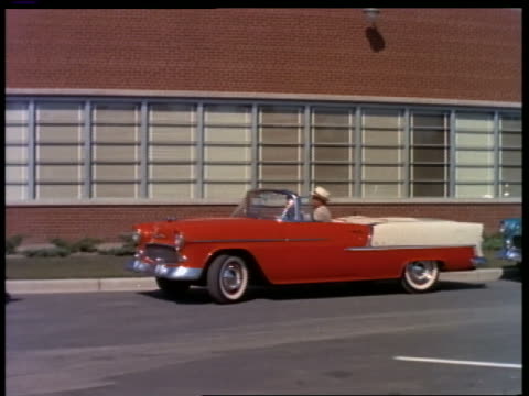stockvideo's en b-roll-footage met 1955 couple parking red + white convertible chevrolet bel air in front of building - 1955
