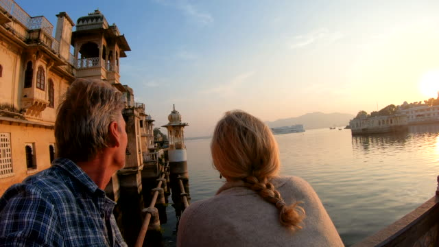 couple pause above lake and floating palace at sunrise - mature couple stock videos & royalty-free footage