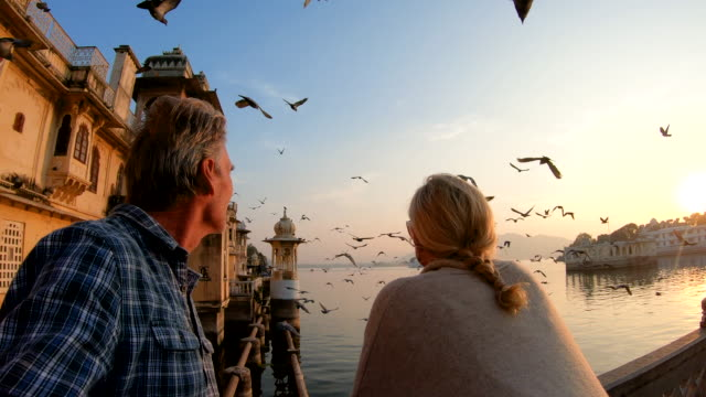 couple pause above lake and floating palace at sunrise - palace video stock e b–roll