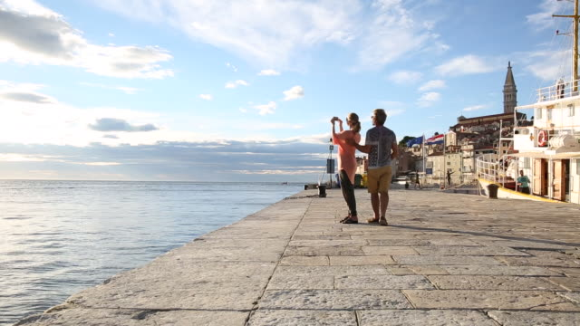 Couple pause at edge of ancient town, look out to sea