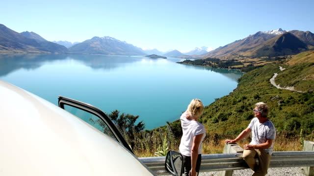 couple pause beside camper van above lake, mtn - road trip stock videos & royalty-free footage