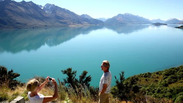 couple pause beside camper van above lake, mtn - schwenk stock-videos und b-roll-filmmaterial