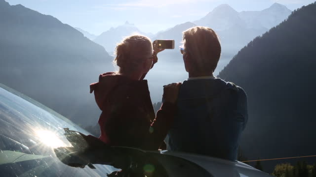 Couple pause besides car to greet sunrise over mountains