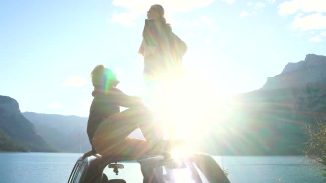 Couple pause by vehicle at mountain lake, sunrise