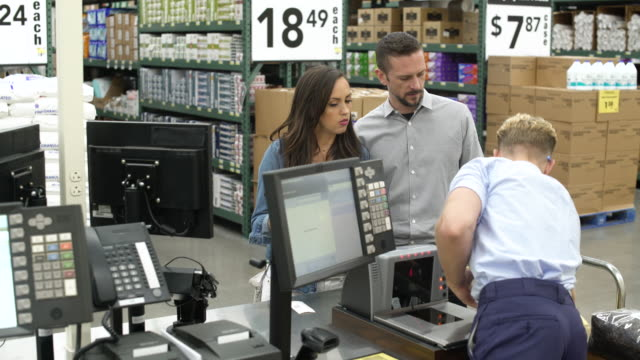 vídeos de stock, filmes e b-roll de couple paying in a warehouse supermarket - vale