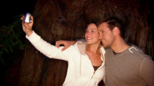 cu, couple photographing themselves, standing by sequoia tree trunk, ragged point, california, usa - ragged point stock videos and b-roll footage