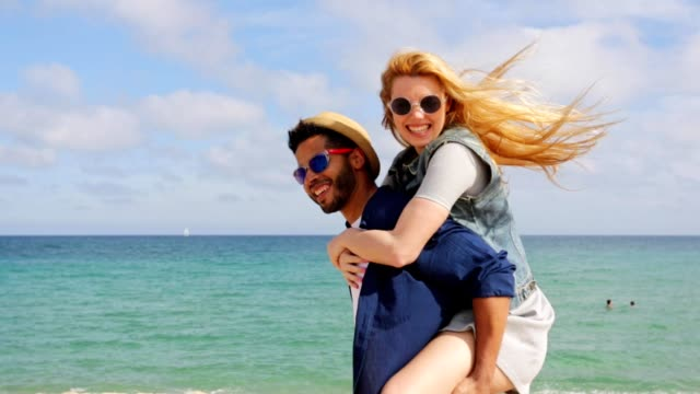 couple piggy backing spinning around by the ocean - piggyback stock videos and b-roll footage