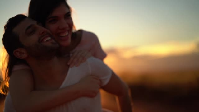 couple piggyback at road trip on sunset time - young couple stock videos & royalty-free footage