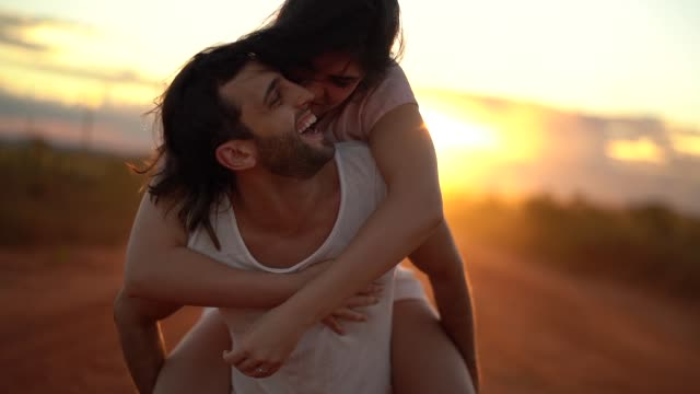 couple piggyback at road trip on sunset time - onirico video stock e b–roll
