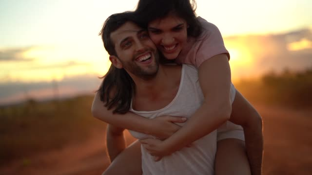 vídeos de stock e filmes b-roll de couple piggyback at road trip on sunset time - carinhoso