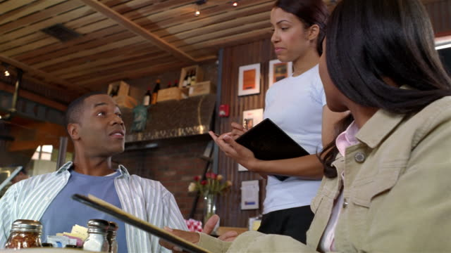 Couple placing order with waitress at restaurant