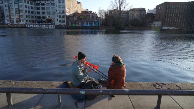 a couple play a trombone and a harmonica on the bank of the spree river on the first day that a new law went into effect temporarily limiting... - couple relationship stock videos & royalty-free footage