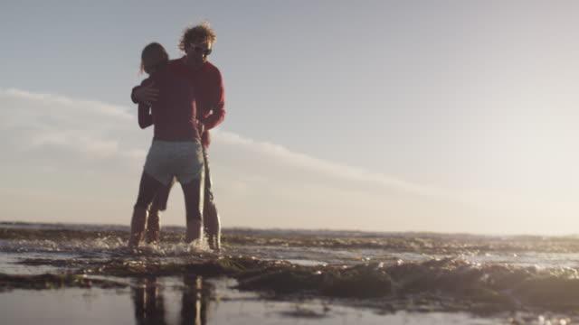 Couple playfully wrestle on beach, sunset