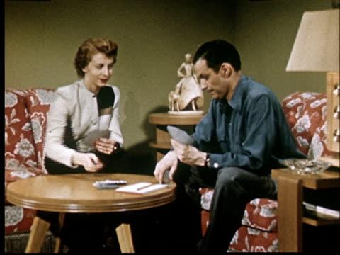 vídeos de stock, filmes e b-roll de ms, couple playing cards in living room - carta de baralho jogo de lazer