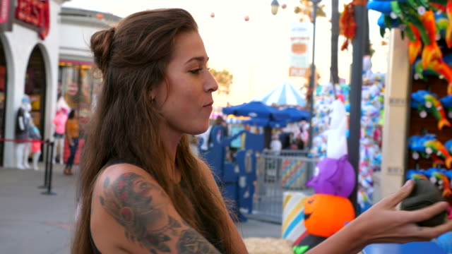 ms couple playing carnival game during date at amusement park - tätowierung stock-videos und b-roll-filmmaterial