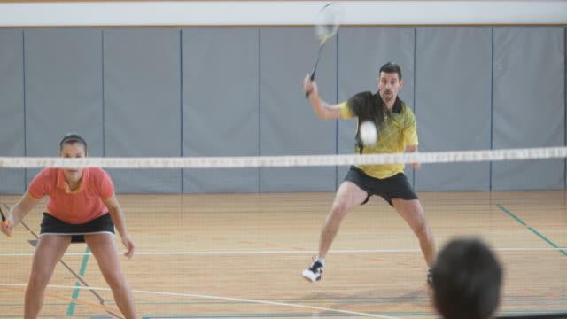 vídeos de stock, filmes e b-roll de casal jogando duplas badminton indoor, marcando um ponto - badmínton esporte