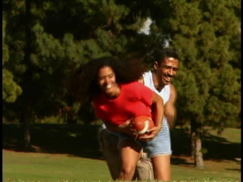 vídeos y material grabado en eventos de stock de couple playing football - encuadre de tres cuartos