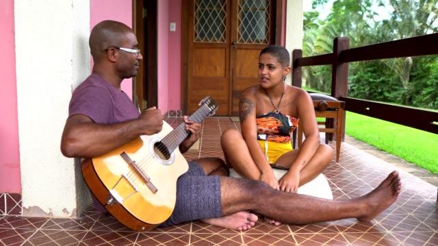 vídeos de stock, filmes e b-roll de casal tocando guitarra e cantando sentado no chão - latino americano