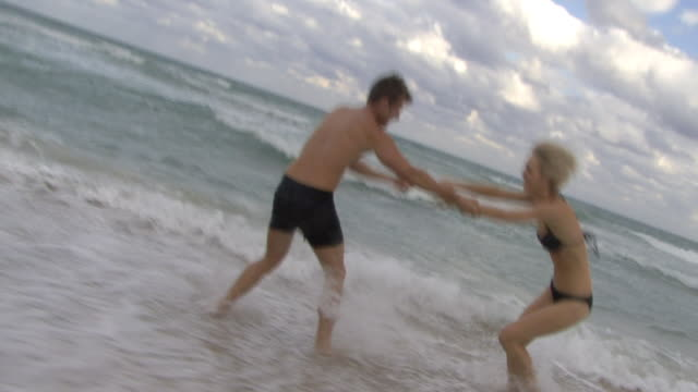 ws couple playing in ocean waves / miami, florida, usa - swimming shorts stock videos & royalty-free footage